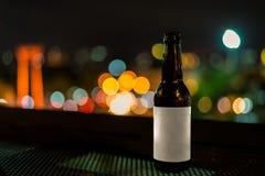Les bouteilles en verre de bière avec la nuit allument le fond de bokeh Photo libre de droits