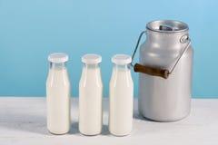 Les bouteilles en verre et le lait peuvent tout près sur le dessus de table en bois Images stock