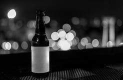 Les bouteilles en verre noires et blanches de bière avec la nuit allument le CCB de bokeh Photos stock