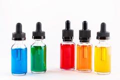 Les bouteilles en verre transparentes remplies ont coloré le liquide avec le compte-gouttes Image stock