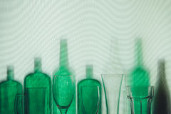 Les bouteilles en verre vertes et les verres de bière vides se tiennent dans le concept de boissons de rangée Photographie stock