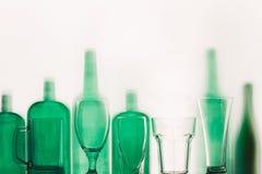 Les bouteilles en verre vertes et les verres vides se tiennent dans le concept de boissons de rangée Photographie stock