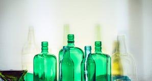 Les bouteilles en verre vertes vides se tiennent dans le concept de boissons de rangée Image libre de droits