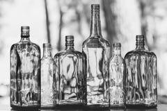 Les bouteilles en verre vides se tiennent dans le concept de boissons de rangée Photos stock