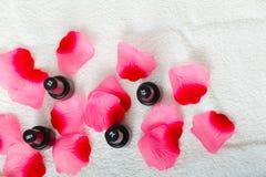 Les bouteilles noires avec vernis à ongles avec des pétales de roses Photos stock