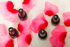 Les bouteilles noires avec vernis à ongles avec des pétales de roses Images libres de droits
