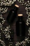 Les bouteilles noires vides de cosmétiques avec de petites fleurs blanches sur le conseil en bois foncé, raillent, vue supérieure Photo stock