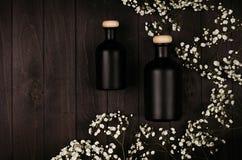 Les bouteilles noires vides de cosmétiques avec de petites fleurs blanches sur le conseil en bois foncé, raillent, vue supérieure Photos libres de droits