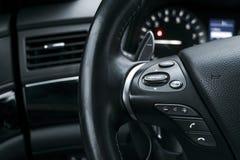 Les boutons de contrôle de media sur volant dedans l'intérieur en cuir perforé noir avec le moniteur d'ordinateur Détail moderne  Photo libre de droits