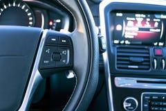 Les boutons de contrôle de media sur volant dedans le cuir noir avec le moniteur d'ordinateur, intérieur moderne de voiture Images libres de droits