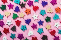 Les boutons de Noël ont découpé hors du bois sur un fond rose images libres de droits