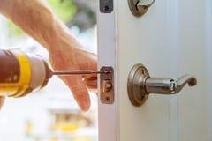 Les boutons de porte intérieure verrouillés par installation, les mains en gros plan de travailleur du bois installent la serrure image libre de droits