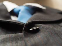 Les boutons noirs sur un ` s d'homme adaptent au fond avec le lien bleu, se ferment  Images stock