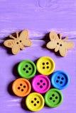 Les boutons ronds en bois lumineux présentés sous forme de fleur sur un Livre vert couvrent, les boutons en bois de papillon Fond Photographie stock libre de droits