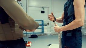 Les boxeurs enveloppe des types de bandage sur leurs mains, plan rapproché de mains banque de vidéos