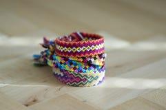 Les bracelets tissés naturels colorés faits maison faits main de l'amitié d'isolement sur le fond bleu-clair, pile de coloré hand Photo libre de droits