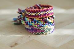 Les bracelets tissés naturels colorés faits maison faits main de l'amitié sur le fond bleu-clair, pile de coloré handcrafts Photos stock