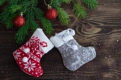 Les branches d'arbre de Noël, les boules, gris rouges et rouge ont tricoté le stockin Photos stock