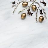 Les branches de saule et d'aulne, les oeufs d'or sur Carrare marbrent contre Image stock