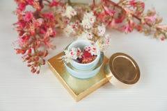 Les branches là blanches et roses de l'arbre de châtaigne, boîte actuelle de Goden avec de la crème de bouteille sont sur le Tabl Photo libre de droits