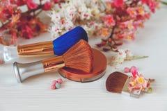Les branches là blanches et roses de l'arbre de châtaigne, de la poudre en bronze avec le miroir et composent Brown et les brosse Images stock