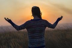 Les bras de fille ont soulevé le coucher du soleil Image stock