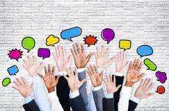 Les bras des hommes d'affaires augmentés avec la bulle de la parole Photo stock