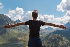 Les bras du jeune homme ont soulevé apprécier la liberté dans les montagnes pendant un jour ensoleillé images stock