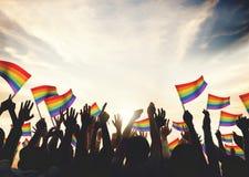 Les bras gais de célébration de foule de drapeau d'arc-en-ciel ont soulevé le concept Photographie stock libre de droits