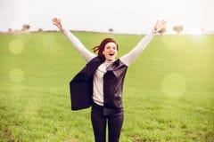 Les bras lèvent la femme sautant dans la campagne Photos stock