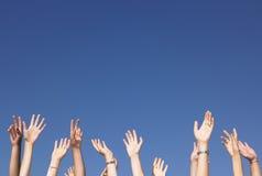 Les bras ont augmenté contre le ciel bleu Photographie stock libre de droits