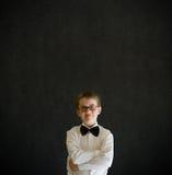 Les bras ont plié le garçon habillé vers le haut de comme l'homme d'affaires Photographie stock