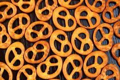 Les bretzels frais croustillants salés se trouvent sur la table photographie stock