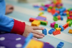 Les briques colorées de contact de main d'enfant jouent sur le plancher de tapis pour jouer photographie stock libre de droits
