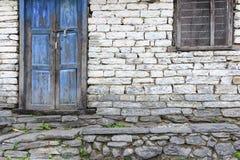 Les briques grises grunges logent le mur avec la porte et la fenêtre bleues Photographie stock libre de droits