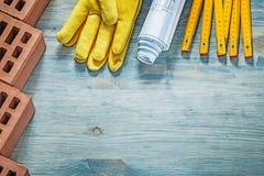 Les briques rouges garnissent en cuir la construction en bois d de mètre de gants protecteurs Images stock