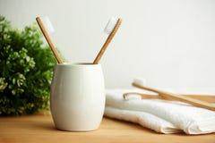Les brosses à dents en bambou dans un verre gris avec l'espace de copie photos stock