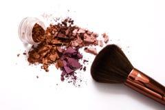 Les brosses de maquillage avec rougissent ou fard à paupières des tons roses, rouges et de corail arrosé sur le fond blanc Photo stock