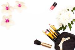 Les brosses de maquillage, le vernis à ongles rose, l'orchidée et le chrysanthème fleurissent sur un fond blanc Concept de beauté Photographie stock