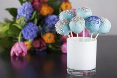 Les bruits bleus de gâteau avec coloré arrose avec de belles fleurs Photographie stock libre de droits