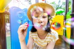 Les bulles de soufflement asiatiques de petite fille sur un terrain de jeu extérieur et regardant la caméra, enfant mignon heureu photo stock