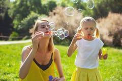 Les bulles de soufflement de maman gaie défraîchissent la fille Images libres de droits