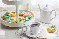 Les butées toriques colorées et délicieuses ont servi avec du café sur la table blanche Image stock