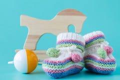 Les butins de bébé avec le bébé cliquettent se reposer sur un fond bleu vert Images stock