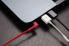 Les câbles d'USB et le cric d'écouteur se sont reliés à l'ordinateur portable Photo stock