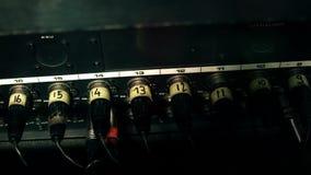Les câbles de XLR ont branché au dos d'un pupitre de contrôle de mélange, nombre-codé banque de vidéos