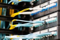 Les câbles optiques se sont connectés au panneau dans la chambre de serveur. Image stock