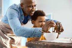 Les céréales fourragères de soin de père à ses fils jouent le dinosaure Image stock
