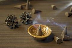 Les cônes exaspèrent dans un support en céramique sur une table en bois Images stock