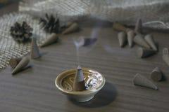 Les cônes exaspèrent dans un support en céramique sur une table en bois Image libre de droits